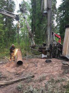 En medarbetare svetsar ett rör i skogen