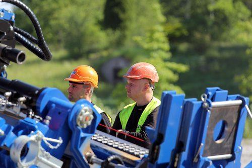 Två medarbetare i varselkläder övervakar arbete