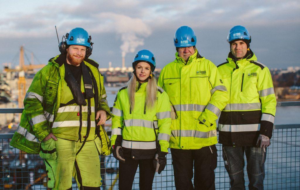 Fyra medarbetare i varselkläder poserar vid Slussen i Stockholm